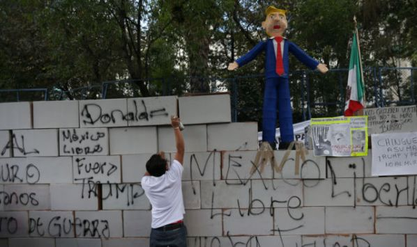 A demonstrator writes on symbolic  wall as is seen a pinata representing the U.S. President Donald Trump during a protest outside the U.S. embassy, in Mexico City